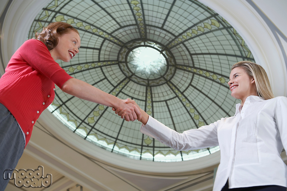 Two women shaking hands under dome low angle view