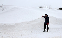 © Licensed to London News Pictures. 3/03/2018. Bodden, UK. A local man stands next to a snow drift on a blocked road at Bodden near Shepton Mallet, Somerset after a week of heavy snow. The snow has taken on the appearance of ice cream after wind has whipped up dust and mud. Photo credit: Jason Bryant/LNP