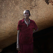 April 28, 2012 - Buram, Nuba Mountains, South Kordofan, Sudan: A Nuba woman stands in front of the cave she uses as a shelter in the mountains outside Buram village in South Kordofan's Nuba Mountains...Since the 6th of June 2011, the Sudan's Army Forces (SAF) initiated, under direct orders from President Bashir, an attack campaign against civil areas throughout the South Kordofan's province. Hundreds have been killed and many more injured...Local residents, of Nuba origin, have since lived in fear and the majority moved from their homes to caves in the nearby mountains. Others chose to find refuge in South Sudan, driven by the lack of food cause by the agriculture production halt due to the constant bombardments of rural areas. (Paulo Nunes dos Santos/Polaris)