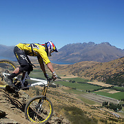 Wyn Masters from New Plymouth in action during the NZBNZ South Island Downhill Cup mountain bike downhill series held on The Remarkables face with a stunning backdrop of the Wakatipu Basin. 150 riders took part in the two day event.  Queenstown, Otago, New Zealand. 9th January 2012. Photo Tim Clayton