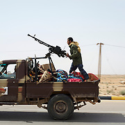 Rebel fighters rush to the frontline during an advance by the Libyan army towards Ajdabiya.