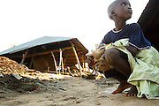 A child crouches near destroyed homes  in the village of Kpoto, Benin on Tuesday October 26, 2010.  Waters have receded in Kpoto, but most of the village was literally flattened by floods that have hit Benin over the past few weeks.