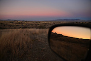 A view of the sunset in a side view mirror while waiting for the moon to rise near Kentucky Camp in the Santa Rita Mountains, Sonoran Desert, Coronado National Forest, Sonoita, Arizona, USA.