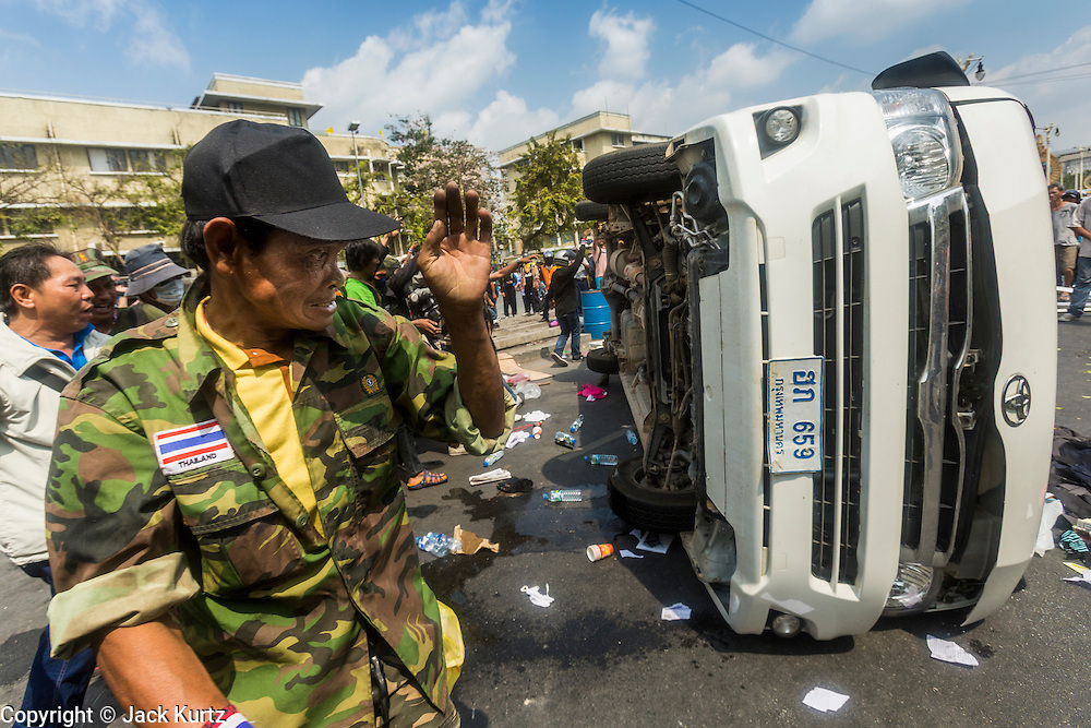 18 FEBRUARY 2014 - BANGKOK, THAILAND: Anti-government protestors attack and overturn a police vehicle in Bangkok. Anti-government protestors aligned with Suthep Thaugsuban and the People's Democratic Reform Committee (PDRC) clashed with police Tuesday. Protestors opened fire on police with at rifles and handguns. Police returned fire with live ammunition and rubber bullets. The Bangkok Metropolitan Administration's Erawan Emergency Medical Centre reported that three civilians and a policeman were killed and 64 others were injured in the clashes between police and protesters.    PHOTO BY JACK KURTZ