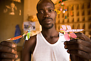 A man holds insects he made from recycled metal cans at the Village Artisanal de Ouagadougou, a cooperative that employs dozens of artisans who work in different mediums, in Ouagadougou, Burkina Faso, on Monday November 3, 2008.