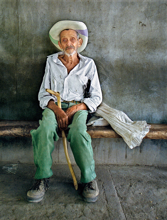 LA REINA, CHALATENANGO, EL SALVADOR- MAY 2000: An old man, viejo hombre, sits in the shade of a small building in the town square.  (Photo by Robert Falcetti). .