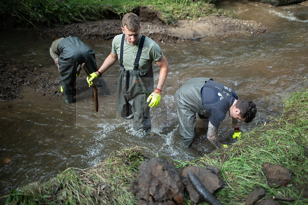 © Licensed to London News Pictures. 04/08/2019. Whaley Bridge, UK. Soldiers from the Light Dragoons regiment , based out of Catterick , work to clear fast-flowing water of debris as water is diverted via a sluice in to a bywater that runs parallel to the reservoir . More rain is forecast overnight (Sunday 4th/Monday 5th August) in the town of Whaley Bridge in Derbyshire after earlier heavy rain caused damage to the Toddbrook Reservoir , threatening homes and businesses with flooding. Photo credit: Joel Goodman/LNP