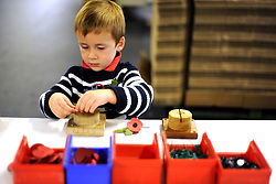 © Licensed to London News Pictures. 07/11/2011. Richmond, UK. Alexander Harding, aged 3,  from Downsend Lodge School, Epsom, assembles a red poppy. Red Poppies being made in The Poppy Factory in preparation for sale in 2012, Richmond, Surrey today 7th November.  The factory has been supplying the poppy, crosses and wreathes to the British Legion for almost 90 years. It is staffed by veterans, many whom of which are injured, sick or wounded of all ages. Photo credit : Stephen Simpson/LNP