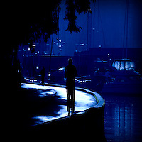 A figure walking along a key side under trees with yachts reflected in the water