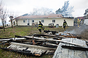Fire fighters carry debris away from a home as multiple fire departments including Milpitas Fire Department, Spring Valley Fire Department, and Cal Fire, work to contain and extinguish a structure fire at the 3000 block of Calaveras Road near Spring Valley Golf Course in Milpitas, California, on February 10, 2014. (Stan Olszewski/SOSKIphoto)
