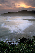 Clouds at sunrise over waves breaking at low tide on the coast at Rocky Creek State Scenic Area, near Newport, Oregon