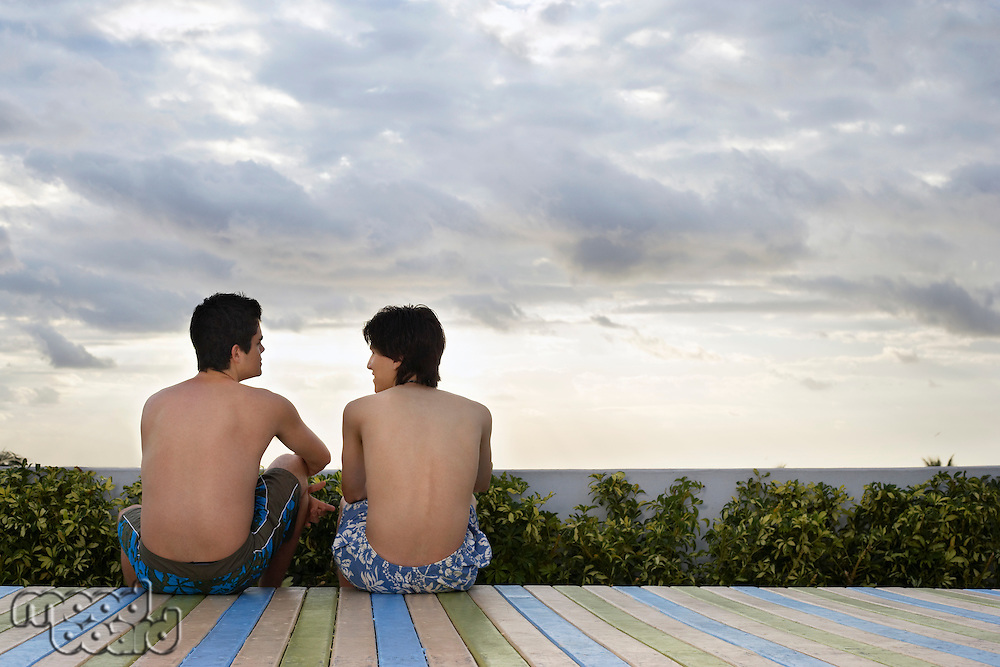 Two teenage boys (16-17) sitting on wooden deck back view