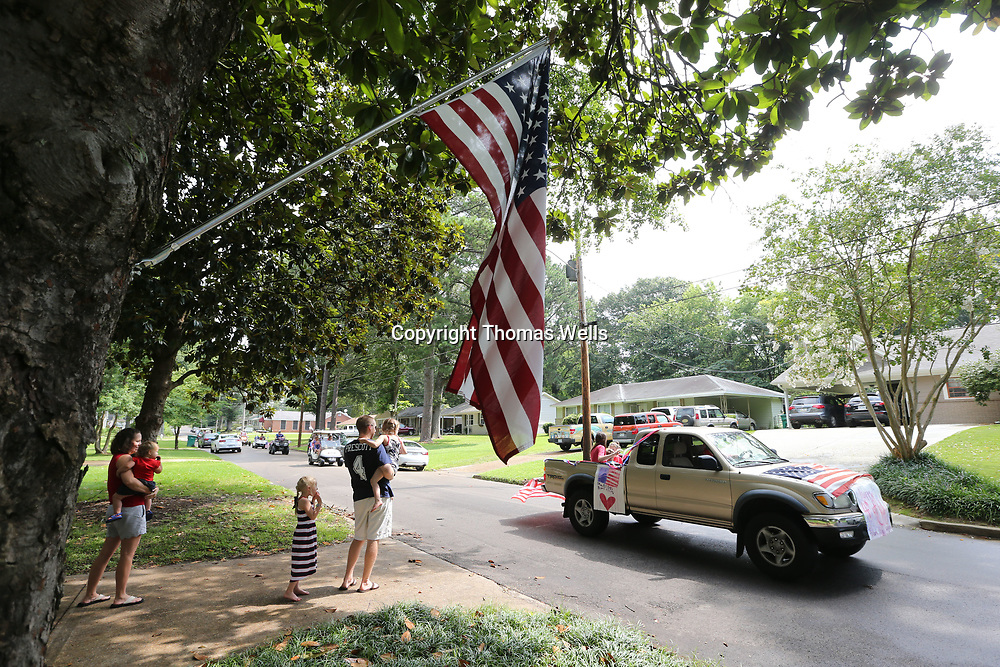 The Willingham family enjoys the annual Joyner Neighborhood parade as it passes by their house on Chester Street Tuesday morning.