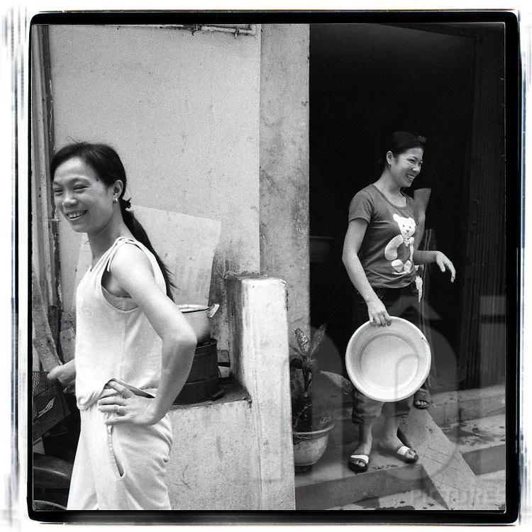 Portrait of two young vietnamese women along the railway of hanoi. One carries a bowl while the other is leaving the place. The women are happy, smile and laugh. One wears a t-shirt printed with a bear.