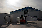 Gansu, China - 25 Feb 2010. A Worker moves a wind turbine rotor at Gansu Jinfeng Wind Power Equipment Co. Ltd. in Jiuquan, Gansu Province, China. China has set a target for renewable energy consumption of 40 percent of the market by the year 2050. Photographer: Markel Rendondo/Greenpeace.