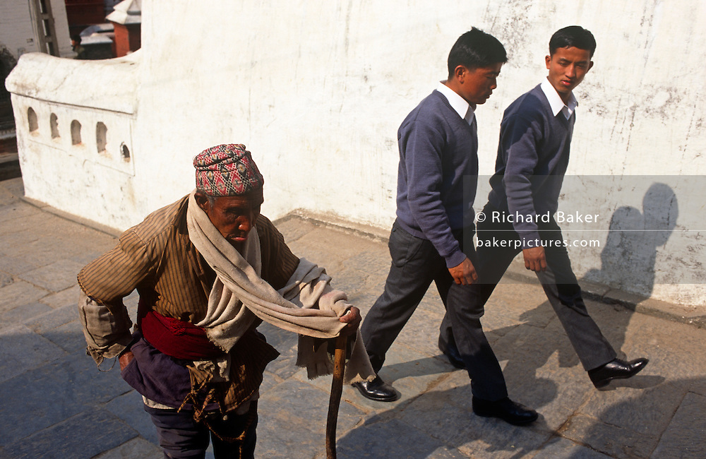 Young Nepali boys stride past poor elderly man in Kathmandu street after recruitment into the British Gurkhas. The recruitment test for the Gurkha Regiment is part of a tough endurance series to find physically perfect specimens for British army infantry training. For example they will need to perform 25 straight-kneed sit-ups at a 45° slant both within 60 seconds to pass. 60,000 boys aged between 17-22 (or 25 for those educated enough to become clerks or communications specialists) report to designated recruiting stations in the hills each November, most living from altitudes ranging from 4,000-12,000 feet. After initial selection, 7,000 are accepted for further tests from which 700 are sent down here to Pokhara in the shadow of the Himalayas. Only 160 of the best boys succeed in the journey to the UK. The Gurkhas have been supplying youth for the British army since the Indian Mutiny of 1857..