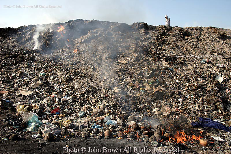 A man walks on top of a huge mound of burning garbage at The Stung Meanchey Landfill in Phnom Penh, Cambodia. Over 700 tons of garbage is sifted through by the workers there each day.