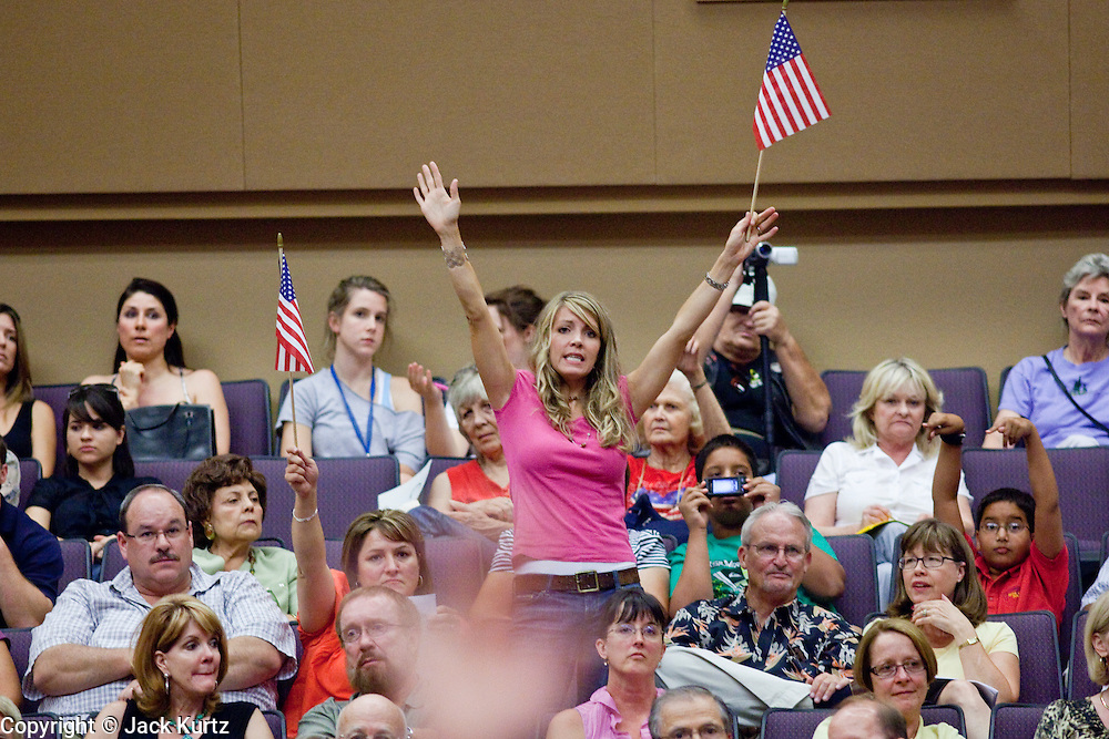 Aug 26, 2009 -- PHOENIX, AZ: SARAH CRAWFORD, from Gilbert, AZ, waves an American flag in support of Sen John McCain at North Phoenix Baptist Church in Phoenix, AZ, Wednesday. She is a supporter of Sen John McCain. Sen McCain hosted his second town hall meeting on health care in two days Wednesday. About 1,000 people attended the meeting. Although most were opposed to President Obama's health care proposals and supported Sen McCain, there was a large group who support the President's health care efforts.  Photo by Jack Kurtz