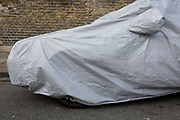 A covered classic car is covered beneath plastic sheeting while parked in a side-street in south London, on 29th January 2019, in Herne Hill, Lambeth, London, England.