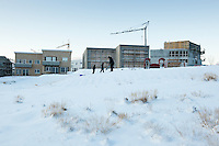 Úlfarsfell suburb in Reykjavík, Iceland. A man ouside with two boys playing in the snow with sleds. Half built appartment houses in background.