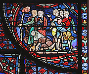 A crowd containing sick and crippled men awaits the arrival of the relics of St Stephen. Pilgrims also came to Chartres to see the Virgin's relics hoping to be cured and the cathedral is here endorsing this act. Section of the crowd gathering around the relics, 1220-25, from the Life of St Stephen and transferral of his relics window in the ambulatory of Chartres Cathedral, Eure-et-Loir, France. This window, unusually dominantly red in colour, tells the story of the life of St Stephen, the first Christian martyr, who died c. 36 AD and whose relics are held at Chartres. It is situated in the chapel dedicated to martyrs. Chartres cathedral was built 1194-1250 and is a fine example of Gothic architecture. Most of its windows date from 1205-40 although a few earlier 12th century examples are also intact. It was declared a UNESCO World Heritage Site in 1979. Picture by Manuel Cohen