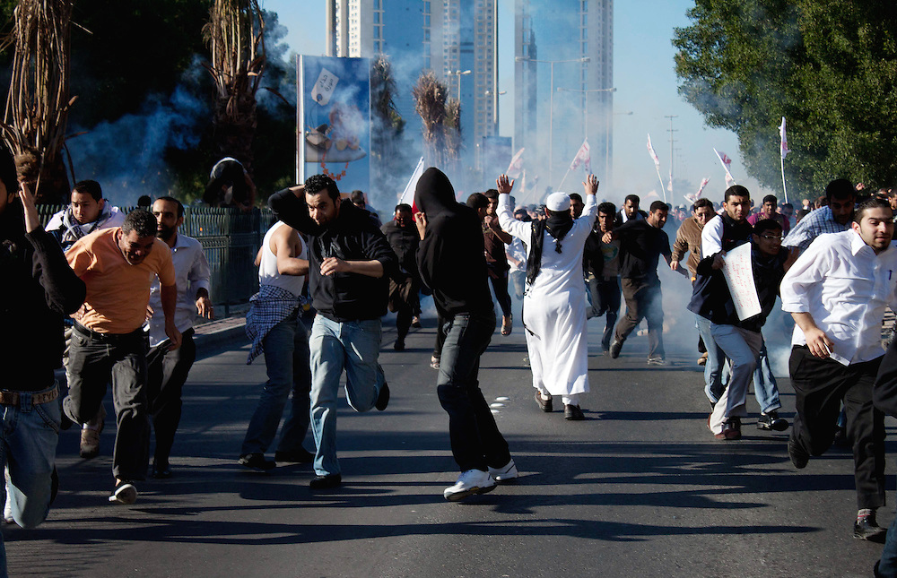 Protesters run from tear gas and live rounds as they are fired upon by police during a march to Pearl Roundabout in Manama, Bahrain.