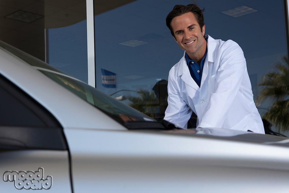 Cheerful car dealer standing besides car