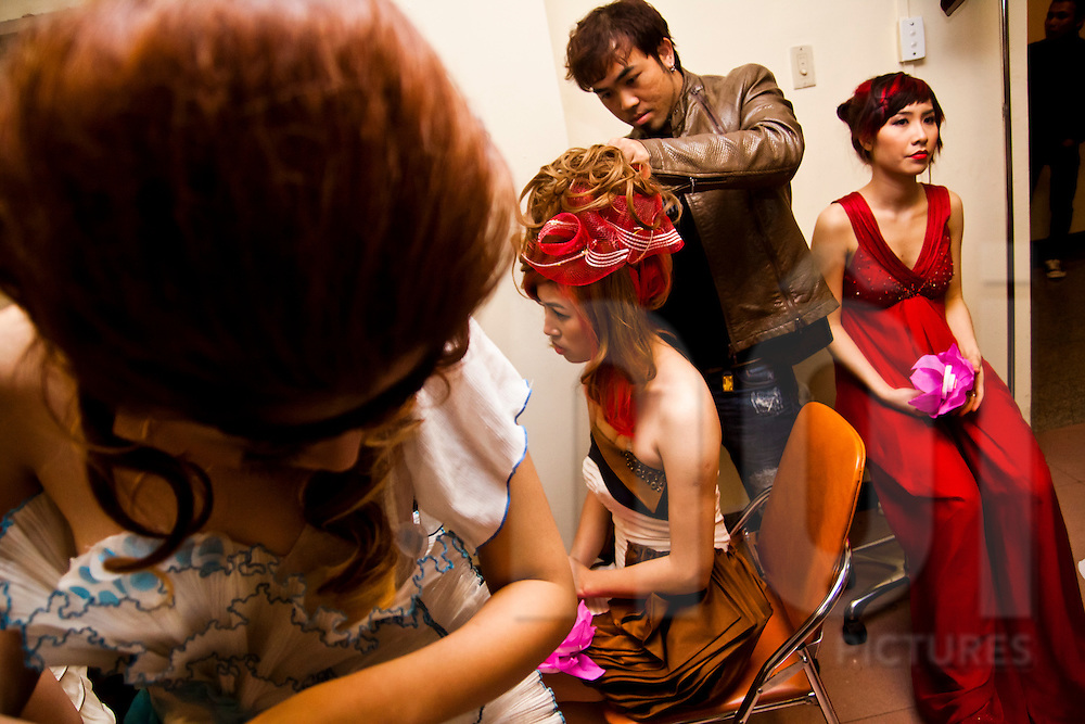 A hairdresser attends to a model backstage at a show in Hanoi, Vietnam