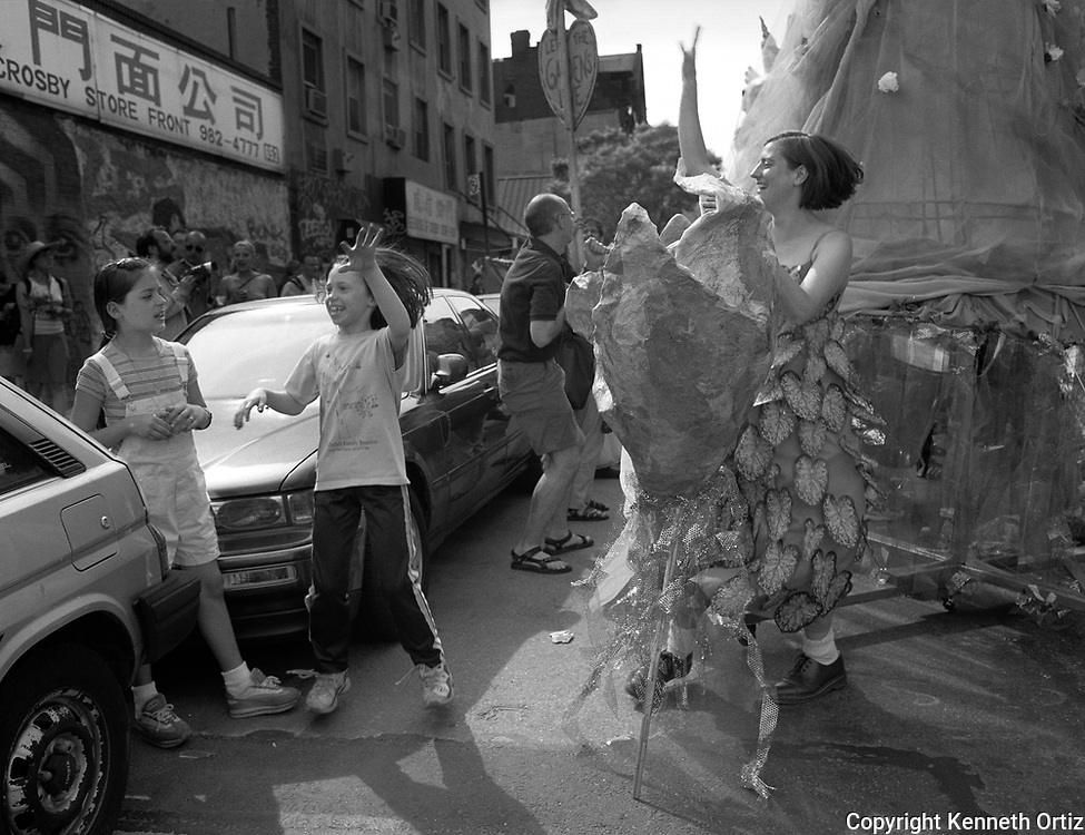 A young woman dancing in a parade on the Lower east side of Manhattan as two kids participate.