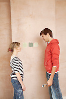 Couple standing face to face choosing paint colour samples on wall