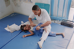 Child with cerebral palsy receiving physiotherapy at centre for rehabilitation and education in Havana; Cuba,