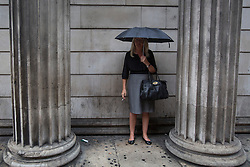 © licensed to London News Pictures. London, UK 30/07/2013. A woman waiting at a bus stop under the rain in City of London on Tuesday, July 30, 2013. Photo credit: Tolga Akmen/LNP