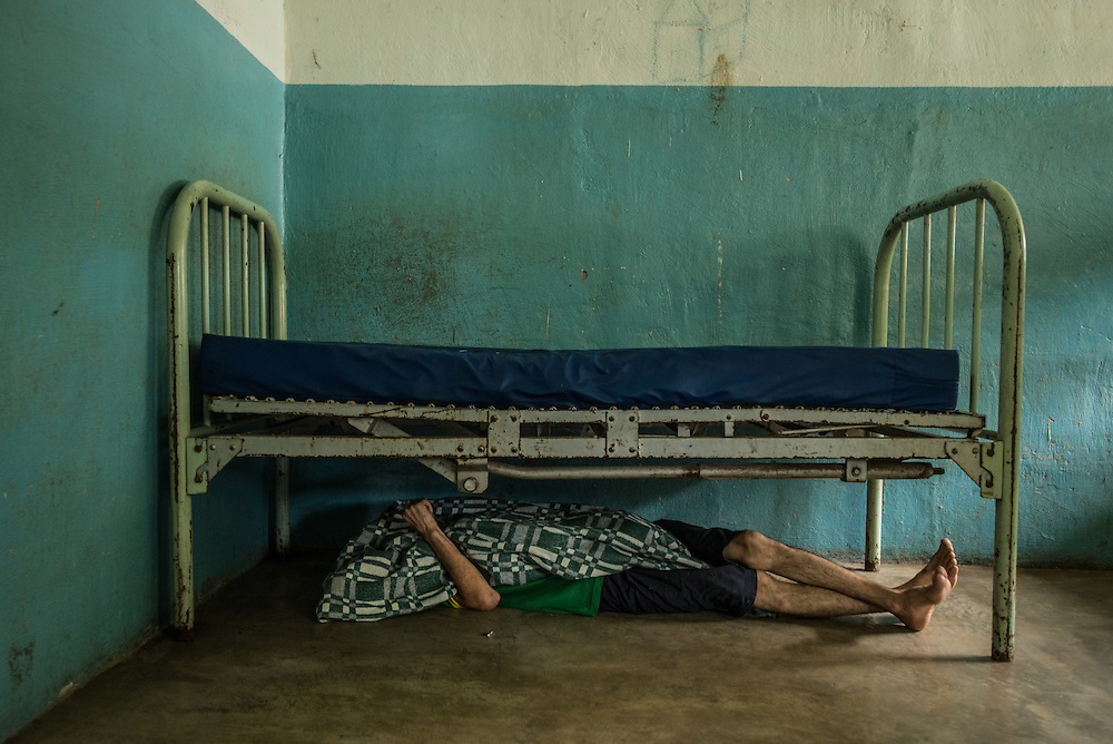 BARQUISIMETO, VENEZUELA - JULY 28, 2016: Raúl Martínez, a paranoid schizophrenic who also suffers from depression, takes a nap under his bed.  He does not have all of the medicines that he needs to keep him stable, because of the shortages.  His skin is infected with scabies.  The economic crisis that has left Venezuela with little hard currency has also severely affected its public health system, crippling hospitals like El Pampero Psychiatric Hospital by leaving it without the resources it needs to take care of patients living there, the majority of whom have been abandoned by their families and rely completely on the state to meet their basic needs. The hospital has not employed a psychiatrist for over two years. Drugs used to combat bipolar disorder, epilepsy, schizoaffective disorder and chronic anxiety are now in short supply, as are numerous sedatives and tranquilizers needed to care for patients. Members of the nursing staff debate daily which patients are the most unstable, to decide which patients will receive pills and which will go without. When a patient loses control, often the only thing they can do is restrain them, or lock them in an isolation cell to prevent them from hurting themselves, other patients and members of the staff.  PHOTO: Meridith Kohut