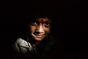 A young boy is found in a small piece of light outiside a tent where a Rajasthani Puja was taking place. They are nomads from the southern state, and travel to north to Manali every year in search of work.