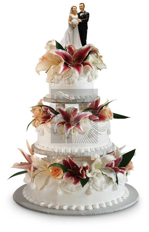 Traditional three layer wedding cake decorated with flowers and a bride and groom ornament on top