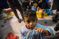 Rasul, three years old and from Baghdad, Iraq, waits with his family and others at the port of Mytilene on the Greek island of Lesbos. They had recently arrived by boat from Turkey, and here are waiting for a ferry to the Greek mainland to continue their migrant journey further into Europe. In the background are his mom, sister, and two young Syrian men.