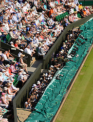 © London News Pictures. 07/07/2013 . London, UK. The crowd and photographers watch as Andy Murray and Novak Djokovic of Serbia compete in the final of the Wimbledon Lawn Tennis Championships. Andy Murray won the match  becoming the first British male to win the tournament in 77 years. Photo credit: Mike King/LNP