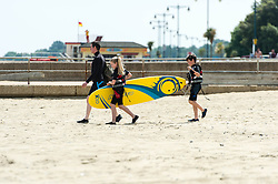 © Licensed to London News Pictures. 14/06/2014. Ryde, Isle of Wight, UK. A family carry a surfboard across the beach to the sea on a hot sunny morning.The UK is experiencing a period of hot sunny weather with temperatures over the weekend expected to reach 74 F (23 C).  Photo credit : Richard Isaac/LNP