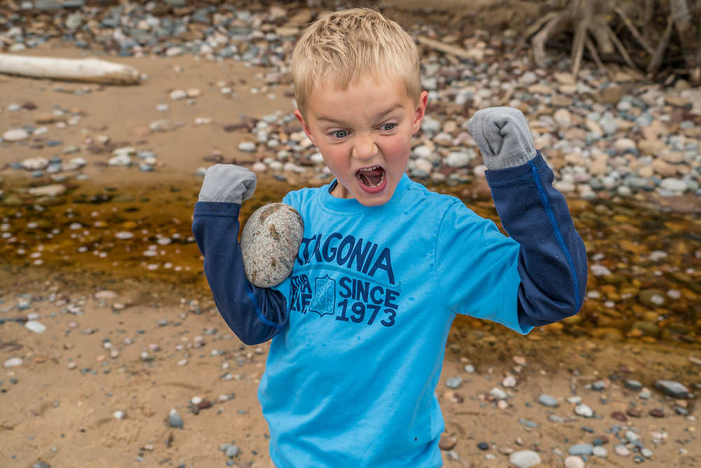 A young boy pretends a rock is his bicep while playing along Lake Superior at Pictured Rocks National Lakeshore near Munising, Michigan in fall.