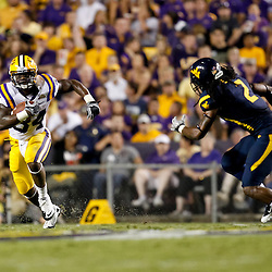 Sep 25, 2010; Baton Rouge, LA, USA; LSU Tigers running back Stevan Ridley (34) is pursued by West Virginia Mountaineers cornerback Robert Sands (2) during the first half at Tiger Stadium.  Mandatory Credit: Derick E. Hingle