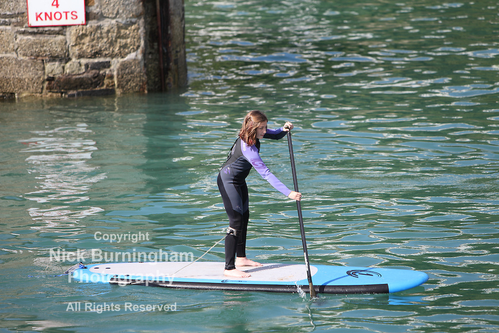 Newquay Harbour, Newquay, Cornwall, August 6, 2015.  High tide and a sunny morning brings a range of tourist activities to Newquay Harbour. Paddle boarding is popular in the calm harbour waters.