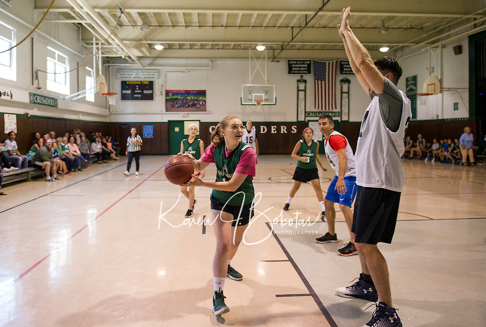 Amelia Hosmer looks to the basket as she gets around Rob Sedgley during the community basketball game with Holy Trinity students against the Laconia Police Dept on Saturday morning.  (Karen Bobotas/for the Laconia Daily Sun)