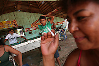 A woman smokes a cigarette in roadside bar in Marcelândia, in Mato Grosso state, in Brazil on April 6, 2008. (Photo/Scott Dalton).