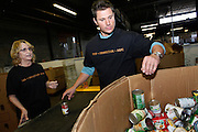 CINCINNATI, OH - OCTOBER 5:  Nick Lachey reaches for canned good while working with a volunteer during the kickoff to The Everybody Wins Tour at Freestore Foodbank on October 5, 2009 in Cincinnati, Ohio. (Photo by Joe Robbins/WireImage for Foodbank)