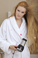 Portrait of a woman using a hairdryer