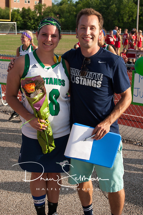 Marquette High School Senior Lacrosse player, Jennifer Slane (28) is honored at halftime against Barat Academy. Coach Chris Elledge, also pictured, read a short bio of each player.  Marquette won the game 15 to 0.