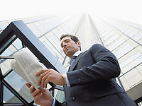 Businessman reading newspaper outside office building (low angle view)