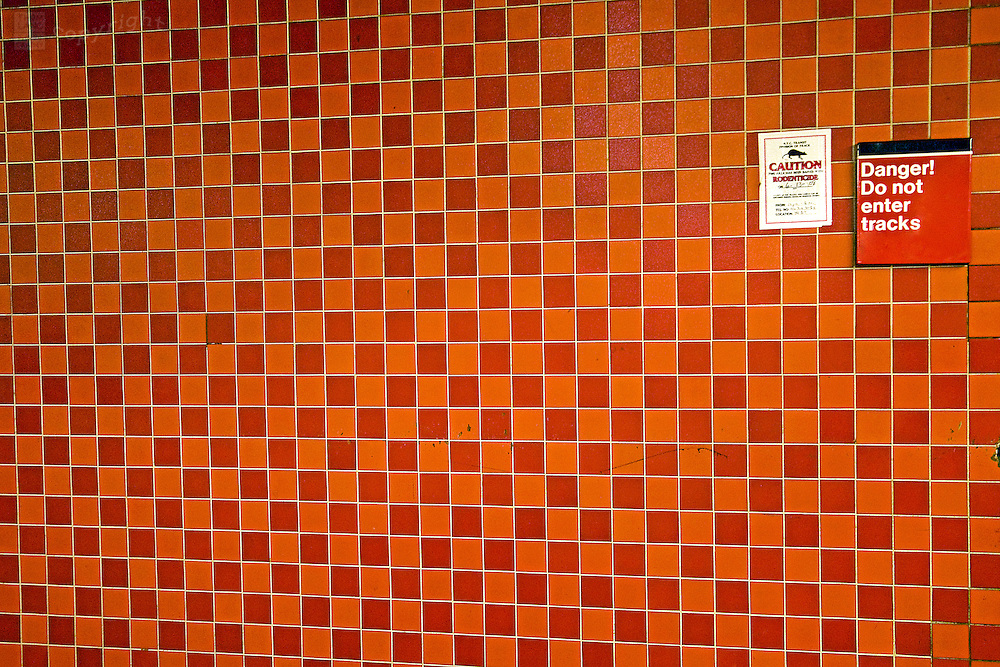 "A sign reads: ""Danger! Do not enter tracks"" on a bright orange and red tiled wall in the New York City subway."