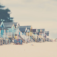 a pair of deck chairs sit in front of a row of beach huts on an english beach