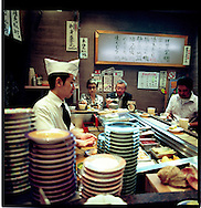 Chef prepares nigiri style sushi at a restaurant where sushi is delivered on a conveyor belt, Shinjuku, Tokyo, Japan.